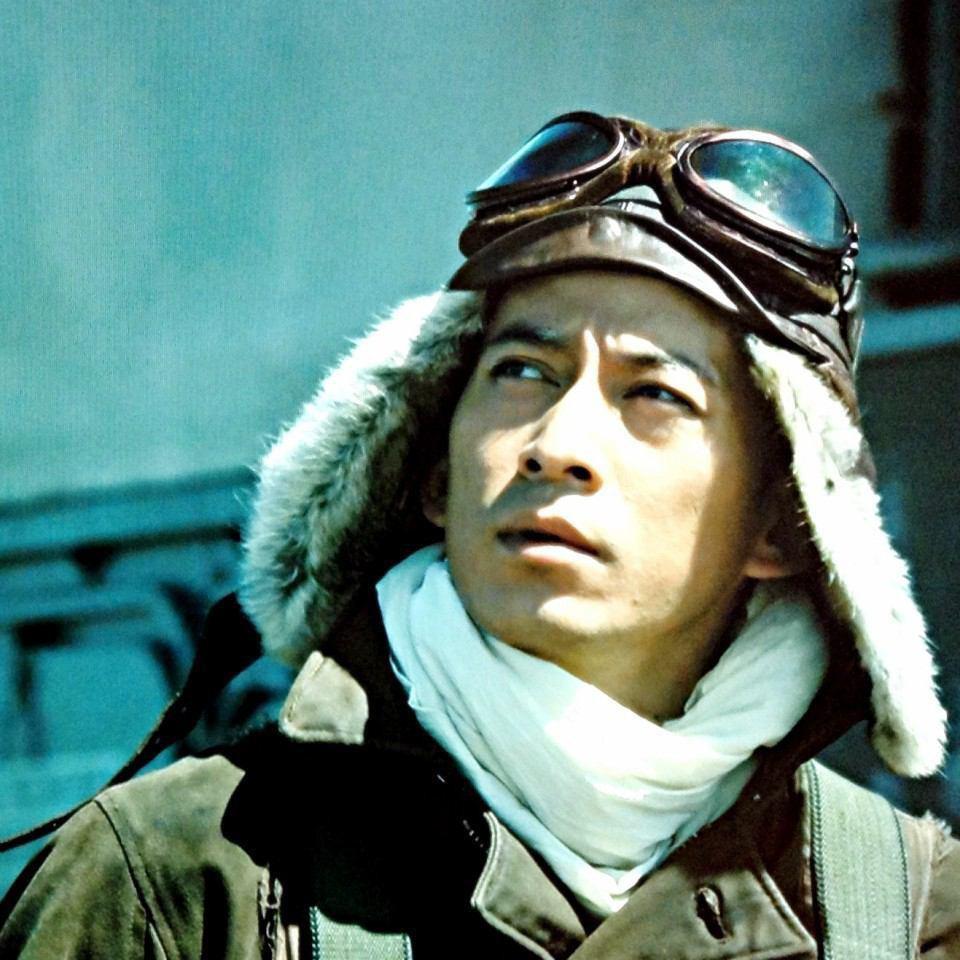 戦闘機に乗る為の戦闘服を着て空を見上げる岡田准一