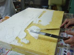 壁のような大きいケーキにクリームを塗ります