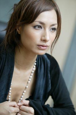 黒いカーディガンにロングネックレスをつけている佐田真由美の画像