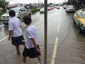 冠水した道を渡る女性学生