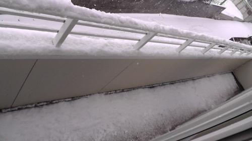 屋根から手すりを経由してベランダに落ちた雪