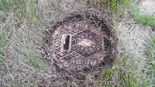 雨水マスのフタを人工芝で隠す