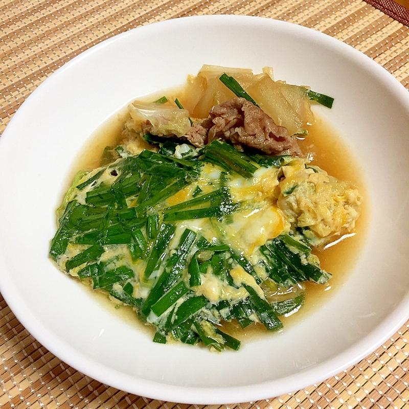 白い丸皿に盛り付けた豚肉と白菜とニラの卵とじ