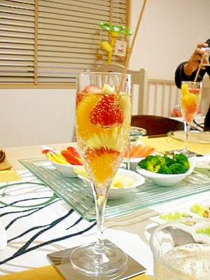 シャンパングラスに注がれたフルーツ入りのフルーツパンチにマドラーが刺さっている