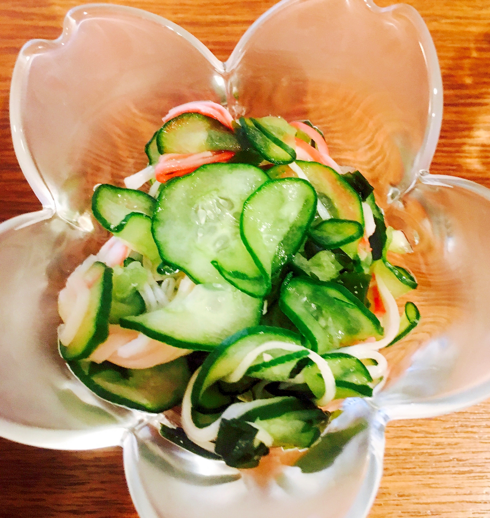 透明の桜型小鉢に盛られた、きゅうりとわかめ+カニカマの酢の物