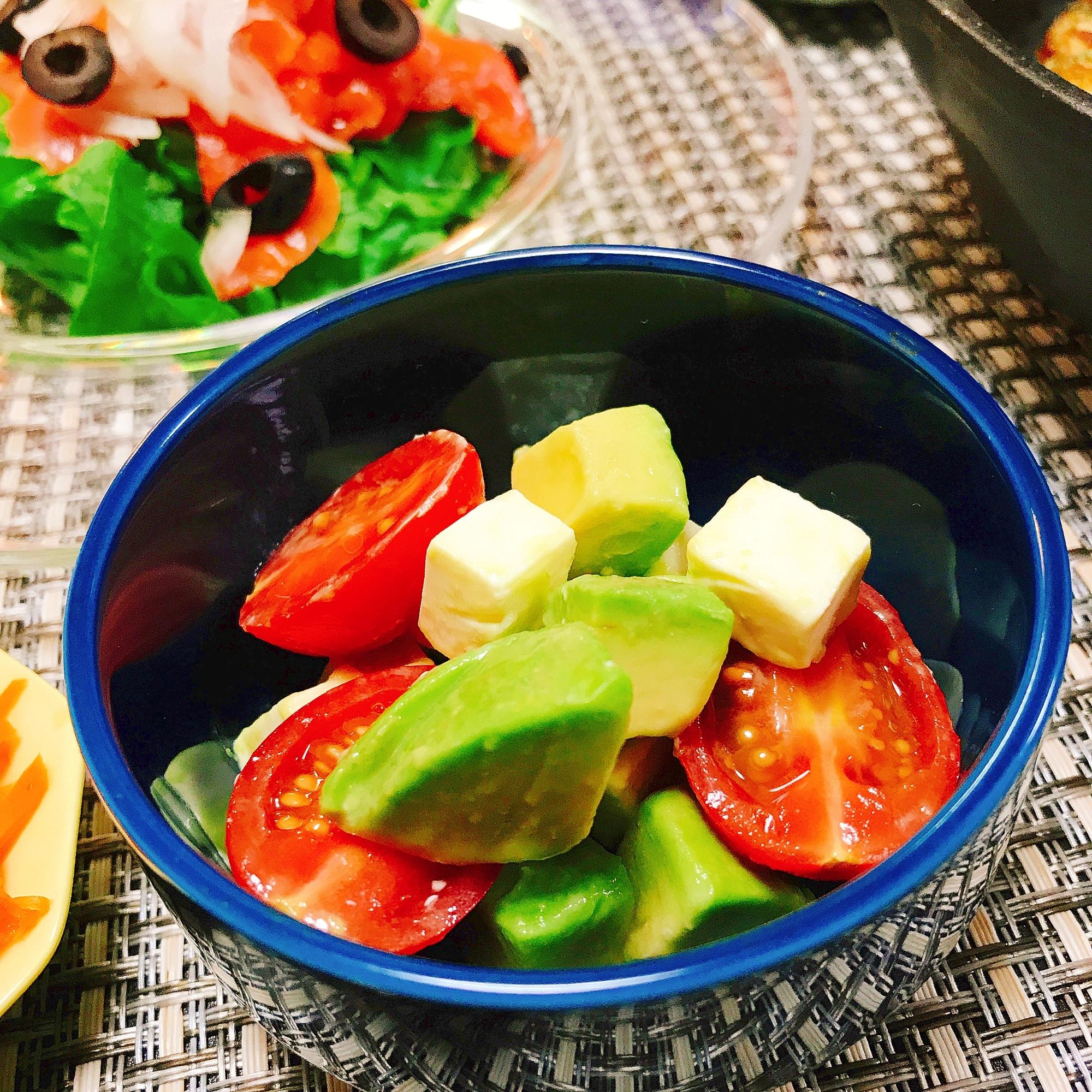 青い皿に入ったアボカドとミニトマトとチーズのサラダ、黒のチェックのクロス