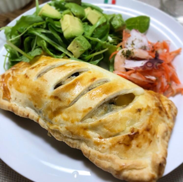白い皿に盛られたパイ包み、アボガドとベビーリーフのサラダ、にんじんとタコのマリネ