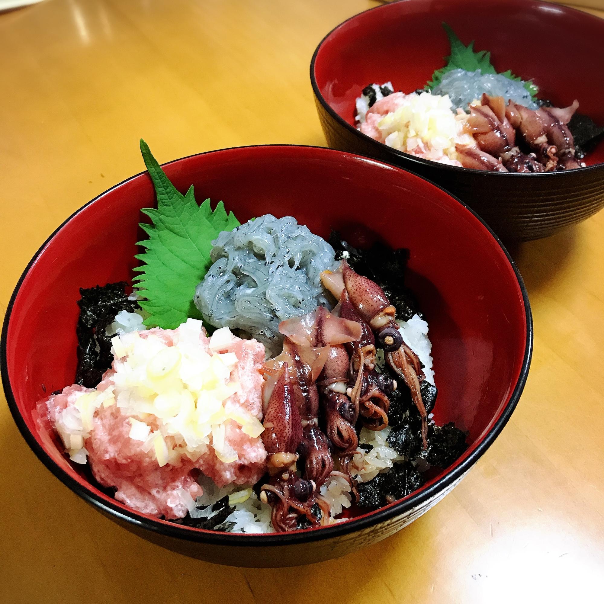 黒い丼に盛り付けた生しらすとネギトロとホタルイカを添えた海鮮三色丼