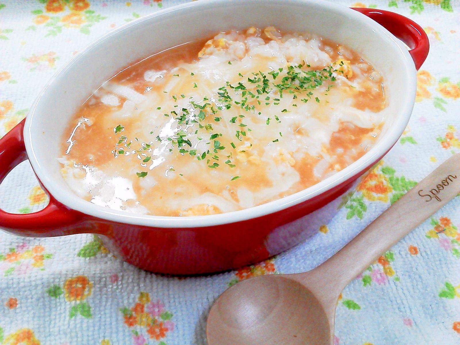両手付きの赤い耐熱皿に盛られた、卵とチーズの洋風雑炊