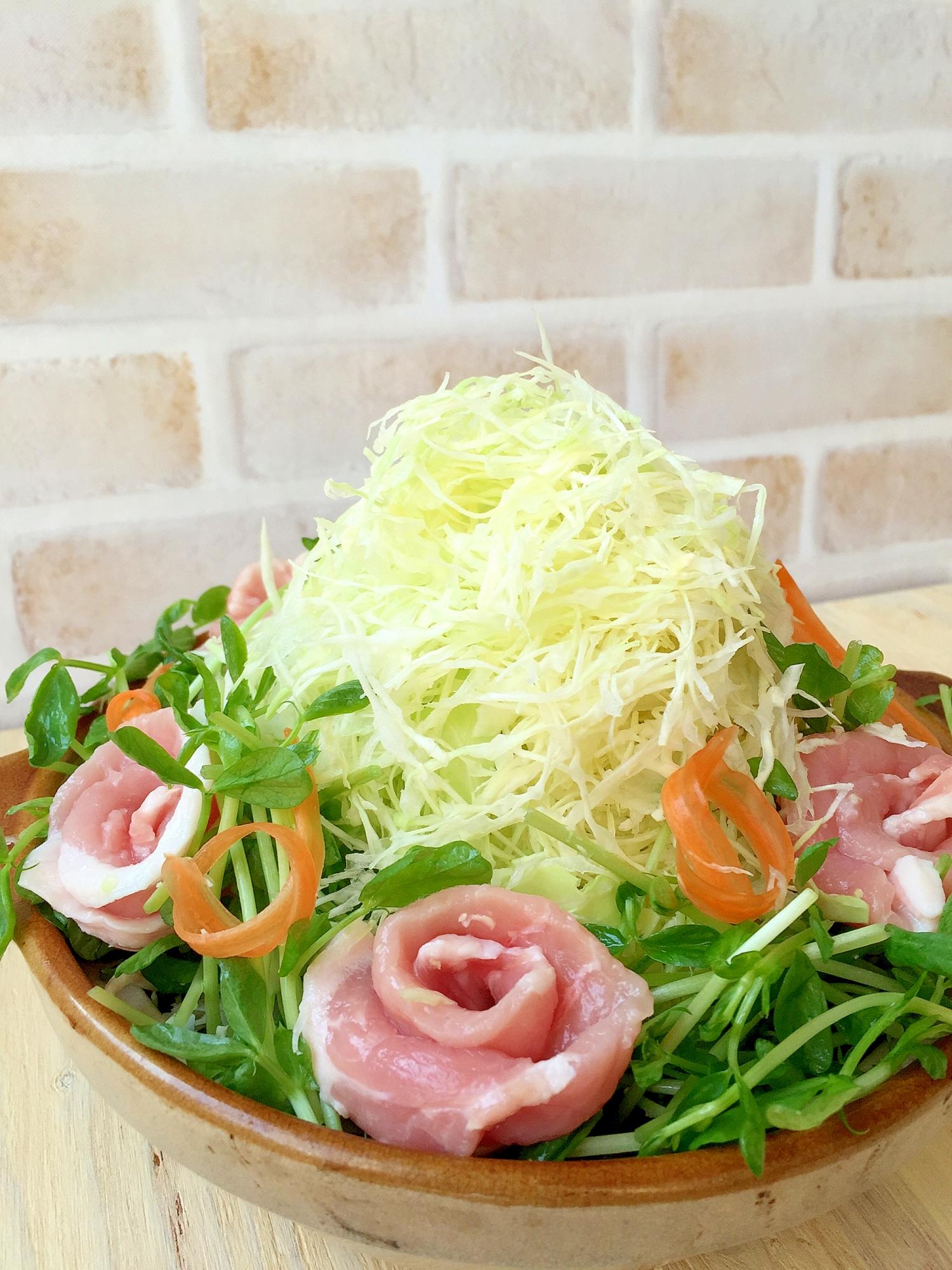 土鍋に高く盛られた千切りキャベツとバラの花びらのような豚肉