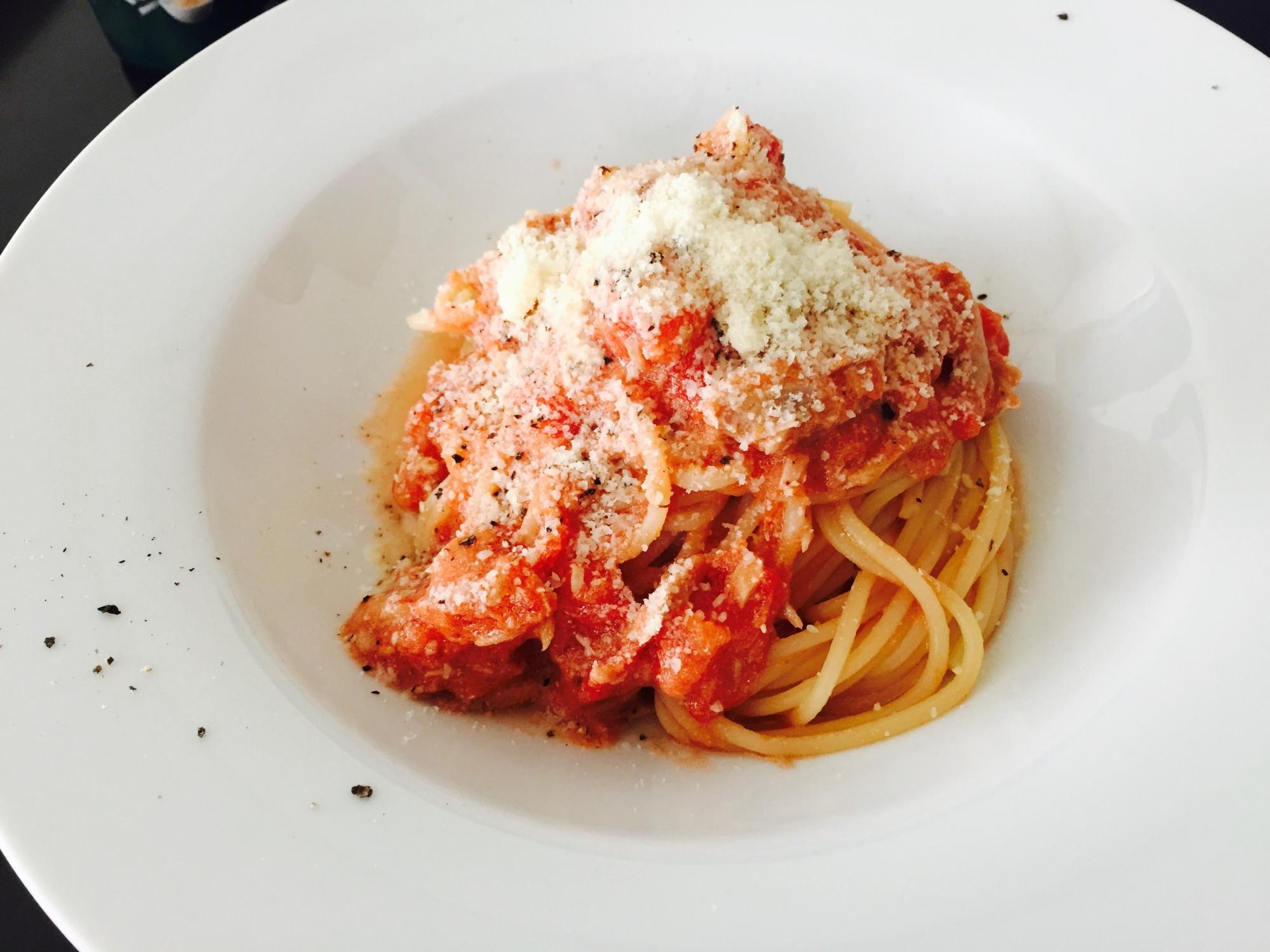白い大皿に盛られた粉チーズのかけられたツナとトマトのクリームスパゲッティ