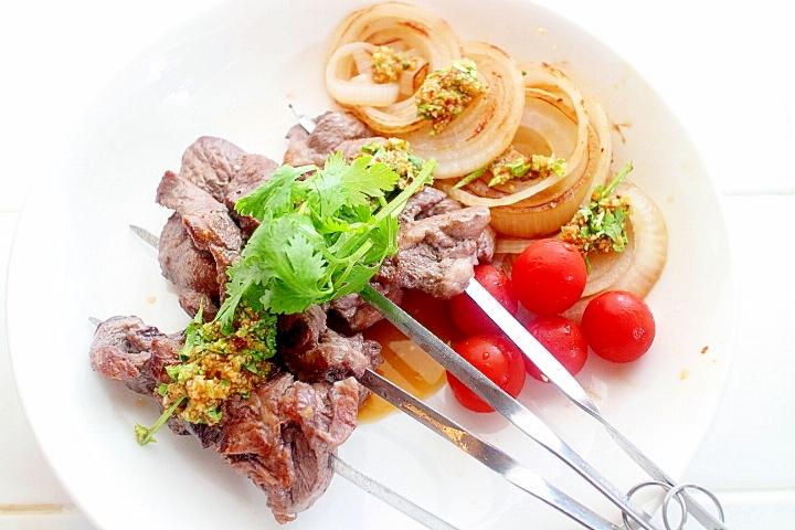 パクチーの特製タレで食べるラム肉の串焼き