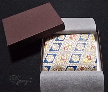 茶色い化粧箱に入った箱まち口金付き二つ折り財布 金唐トランプ