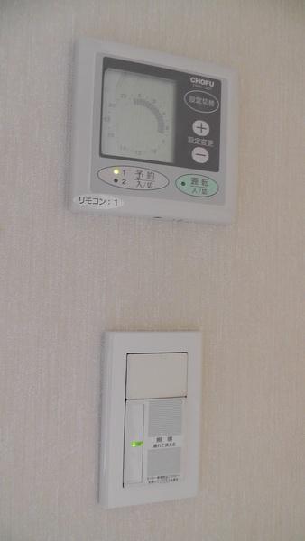 1階キッチンの勝手口にある床暖房用コントローラーと照明用スイッチ
