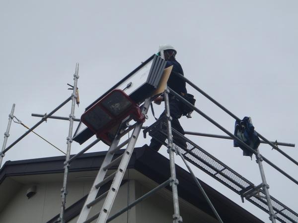太陽電池パネルをリフトで屋根に上げる
