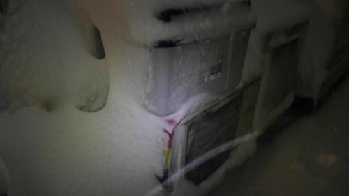雪に埋もれそうな室外機
