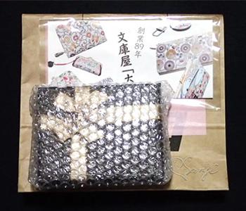 プレゼント包装されエアキャップに包まれた金唐 箱まち口金付き札入れ 二つ折り財布