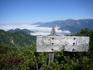 風雪に耐える看板、左の3つこぶは滝倉山とサンナビキ山