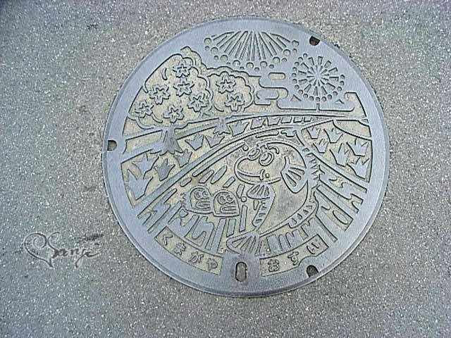 ムサシトミヨとサクラや花火がデザインされた八王子市のマンホールの蓋
