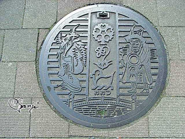滋賀・大津絵の「藤娘」と「鬼の寒念仏」をデザインしたマンホールの蓋