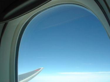 雲を引きながら高く飛ぶ飛行機